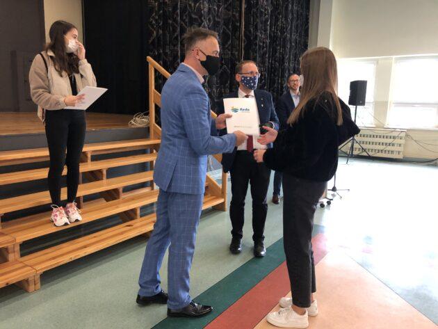 Stypendystka odbiera nagrodę zrąk Łukasza Kamińskiego Zastępcy Burmistrza Miasta Redy orazRadnego Rady Miejskiej wRedzie Leszka Hebla